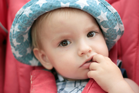 perceptive: A toddler blond boy looking musingly and thoughtfully and putting his finger on the mouth, close-up emotional portrait, outdoors Stock Photo