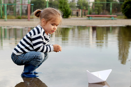 Funny little kid girl in rain boots playing with white paper ship in a puddle on warm summer day. Active leisure for children, family weekend, summer outdoors