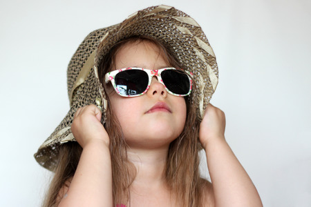 Cute happy baby girl wearing swimming suit, sun glasses and hat over white background, summer vacation concept