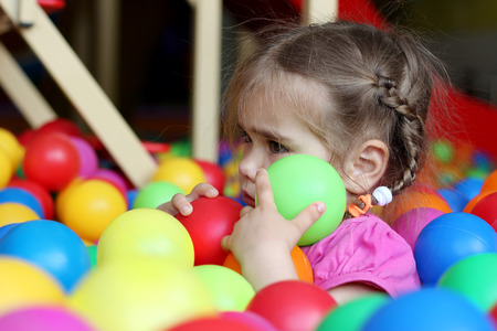 negative area: Sad little girl among colorful balls, family weekend concept, birthday and party, do not want to go home