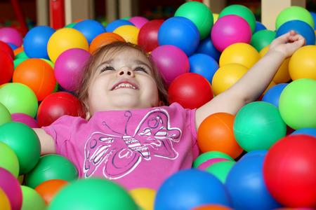 Šťastná dívka hraje a baví se v mateřské škole s barevnými kuličkami, rodinným víkendovým konceptem, šťastnými narozeninami a veselou party