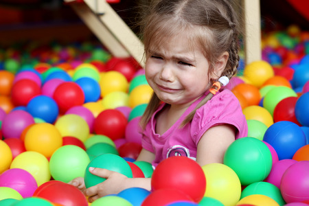 negative area: Crying little girl among colorful balls, family weekend concept, birthday and party, do not want to go home