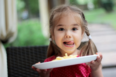 Beautiful laughing little girl sitting at table and holding a plate with French fries, food and drink concept, outdoor portrait