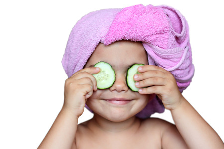 Funny small girl with cucumbers on eyes and a bath towel on her head over white background, beauty and health concept, indoor closeup portrait