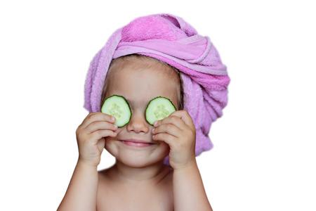 흰색 배경, 아름다움과 건강 개념, 실내 근접 촬영 초상화 위에 그녀의 머리에 눈과 목욕 수건에 오이와 재미있는 작은 소녀