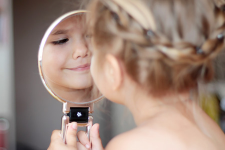 nude little girls: Lovely little girl smiling to her reflection in a round mirror, closeup portrait