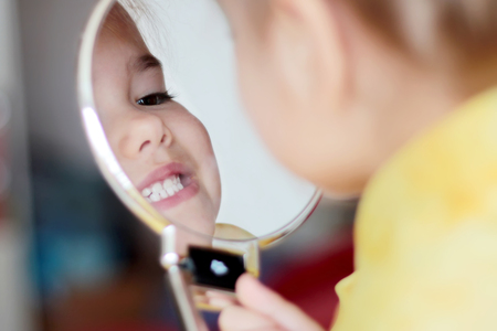 Cute little girl examining her mouth and teeth in the mirror, close-up, medical and health concept