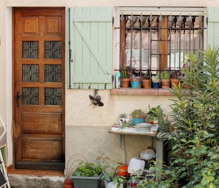 puertas de madera: antigua casa típica de un pueblo en La Provenza, puertas de madera con flores cerca de la puerta, hermosa vista, al aire libre Foto de archivo