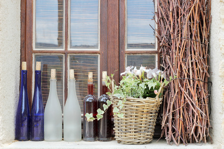 Window with old wine bottles, white and blue, a pot with flowers petunia and handful of brushwood, decoration and design in Provence style, summer outdoor Stock Photo