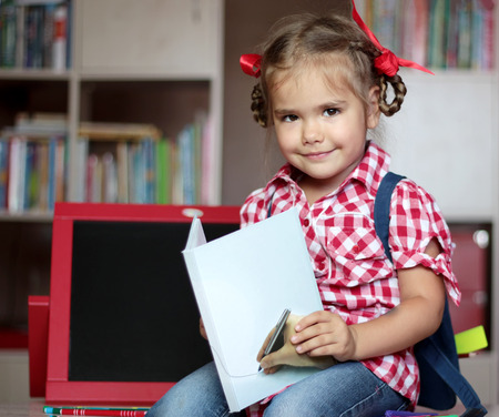 implements: Portrait of cute smiling girl with school implements sitting near the copybook, backpack and colorful pencils, education and back to school concept Stock Photo