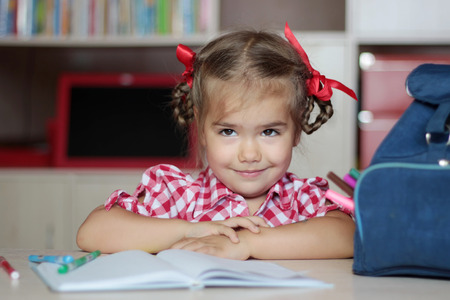 writing implements: Portrait of cute smiling girl with school implements sitting near the copybook, backpack and colorful pencils, education and back to school concept Stock Photo