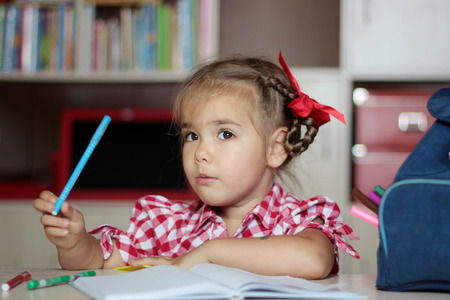 implements: Portrait of cute thoughtful girl with school implements sitting near the copybook, backpack and colorful pencils, education and back to school concept