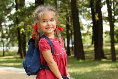 niños saliendo de la escuela: Niña hermosa con la mochila caminando en el parque listo de nuevo a la escuela, caída al aire libre, concepto de la educación