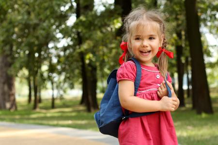 Niña hermosa con la mochila caminando en el parque listo de nuevo a la escuela, caída al aire libre, concepto de la educación