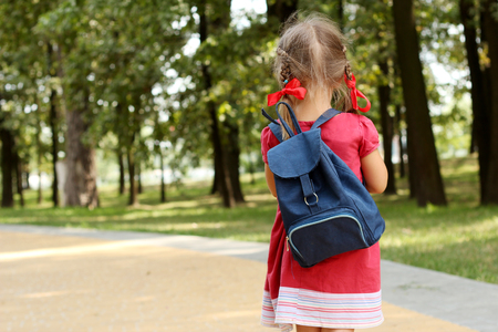 Beautiful little girl with backpack walking in the park ready back to school, back view, fall outdoors, education concept
