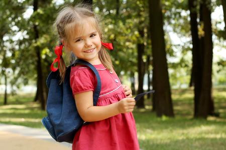美しい少女、学校に行く準備ができての公園を歩いてバックパックで落ちる屋外の教育概念 写真素材