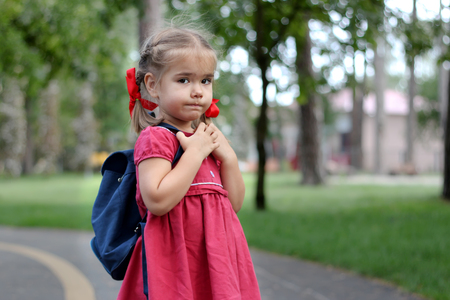 Beautiful little girl with backpack ready back to school, fall outdoors, education concept Stock Photo