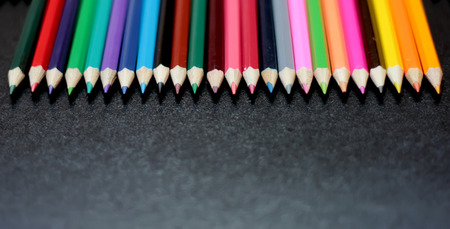 writing implements: Colorful pencils arranged over blackboard background, place for text, selective focus, education and back to school concept