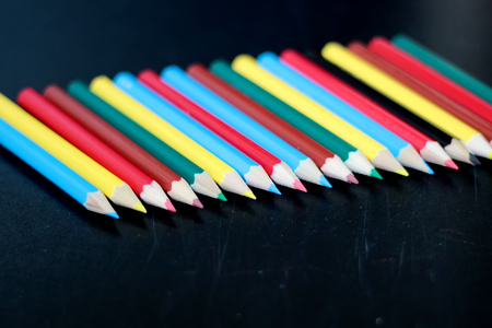 Colorful pencils arranged over blackboard background, place for text, selective focus, education and back to school concept