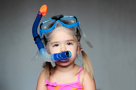 swim mask: Little girl wearing a diving mask over grey background, swim and sport concept