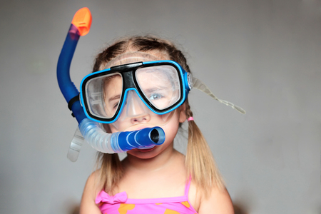 swim mask: Little girl wearing a diving mask over grey background, focus on the mask, swim and sport concept
