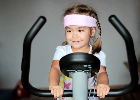 hometrainer: Healthy little girl training at home with exercise bike, healthy lifestyle concept
