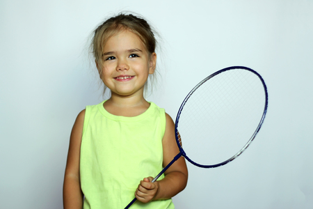 racquet: Pretty small girl in yellow t-shirt with badminton racquet over white background, indoor portrait, sport and health concept