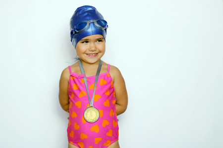 Pretty small girl in pink swimwear and goggles with gold medal on her neck over white background, indoor portrait, sport and health concept Stok Fotoğraf