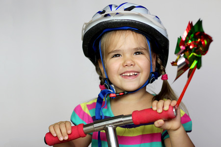 Smiling little girl in bike helmet and striped t-shirt holding the handle bar of push-bicycle, sport and recreation concept