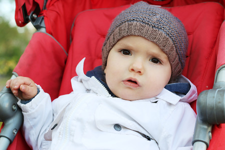 Thoughtful baby in the knitted hat sitting in the stroller, outdoor portrait