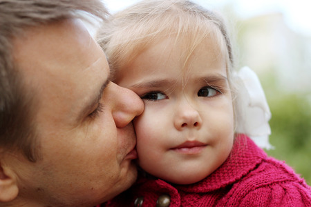 A man kissing a beautiful little girl with bows and looking on her with tenderness and love, outdoor portrait