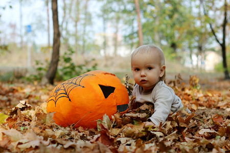 masque: Cute toddler boy playing with pumpkin masque in the autumn park, outdoor