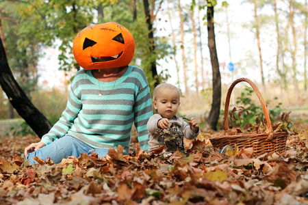 Handsome toddler sitting on the leaves near the adult in pumpkin mask on her head in the autumn park