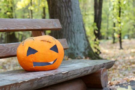 papiermache: Pumpkin papier-mache mask laying on a wooden bench in the autumn park