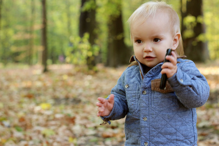 toddler walking: Handsome toddler walking in the autumn park and speaking on the mobile telephone