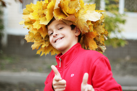 Happy teenager in maple wreath, fall outdoor