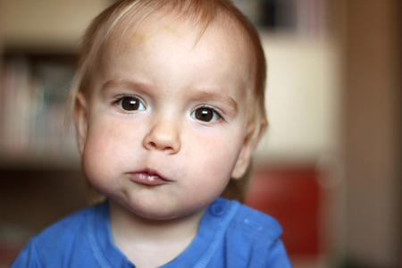 Cute blond baby boy with puffed-out cheek because of sugar candy, indoor portrait