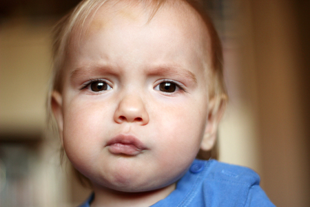 tightened: Sad blond baby boy with serious fun grimace and tightened mouth, indoor portrait