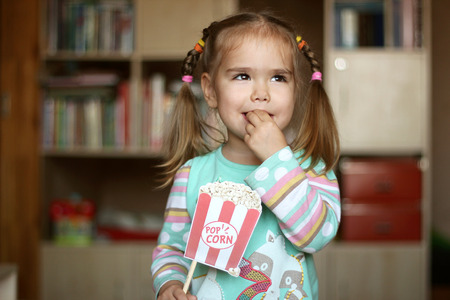 Pretty toddler girl for fun eating popcorn paper decoration, indoor portrait Stock Photo