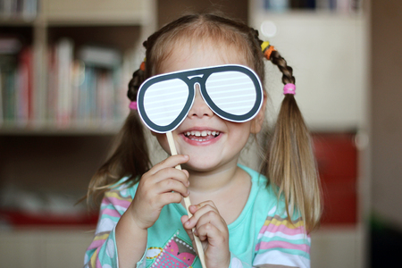 Pretty toddler girl for fun trying on paper glasses decoration, indoor portrait