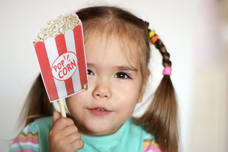 Pretty toddler girl with popcorn paper decoration, indoor portrait Stock Photo