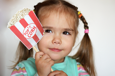 Dreaming pretty toddler girl with popcorn paper decoration, indoor portrait Stock Photo