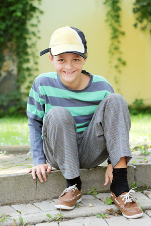 Smiling arch teenager with the cap sitting on border and putting on his shoe, autumn outdoor