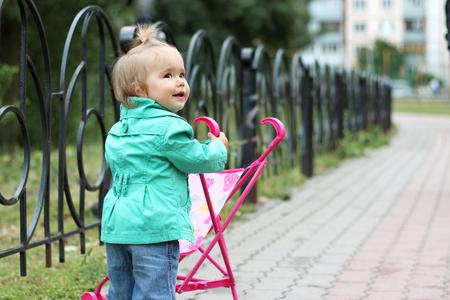 niño empujando: Elegante niño pequeño que desgasta la capa verde, empujar el cochecito de juguete y mirar a su alrededor, al aire libre en el parque de la ciudad