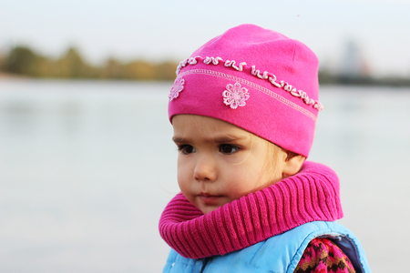 Serious toddler on the autumn beach against blue sky