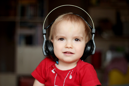 gesticulate: Cute toddler boy listening to music in big head-phones, close-up indoor portrait