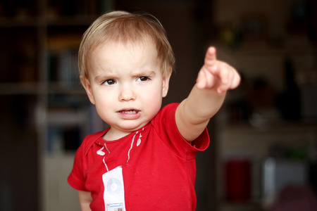 exacting: Serious toddler boy wearing in a red T-shirt points a finger to something, people gesture concept, emotional indoor portrait Stock Photo