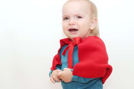 whimper: Crying toddler (boy) dressed as a superhero over white background, indoor portrait, superhero concept