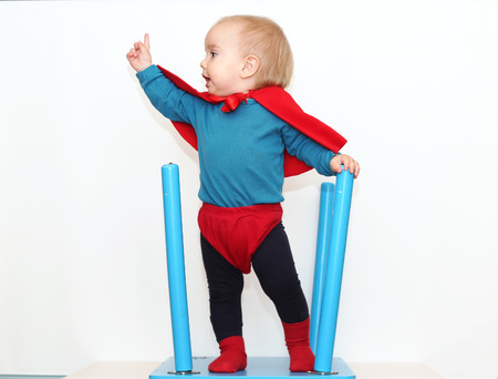 Funny toddler (boy) dressed as a superhero over white background, indoor portrait, superhero concept