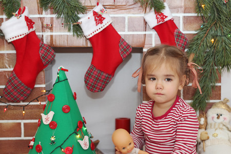 Pretty sad child girl sitting near Christmas decorated tree and fireplace, winter holiday family concept Stock Photo